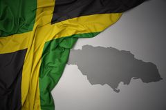 Waving colorful national flag and map of jamaica. Waving colorful national flag of jamaica on a gray map background royalty free stock images