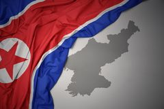 Waving colorful national flag and map of north korea. Waving colorful national flag of north korea on a gray map background stock photos