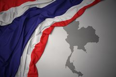 Waving colorful national flag and map of thailand. Waving colorful national flag of thailand on a gray map background stock photography