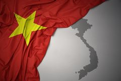 Waving colorful national flag and map of vietnam. Waving colorful national flag of vietnam on a gray map background royalty free stock image