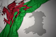 Waving colorful national flag and map of wales. Waving colorful national flag of wales on a gray map background stock photos