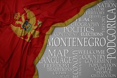 Waving colorful national flag of montenegro on a gray background with important words about country. Concept royalty free stock image