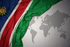 Waving colorful national flag of namibia. Waving colorful national flag of namibia on a gray world map background Stock Image