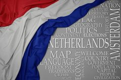 Waving colorful national flag of netherlands on a gray background with important words about country. Concept royalty free stock photos