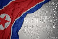 Waving colorful national flag of north korea on a gray background with important words about country. Concept royalty free stock photography