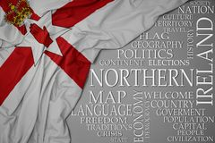 Waving colorful national flag of northern ireland on a gray background with important words about country. Concept royalty free stock image