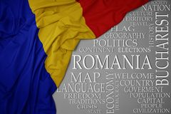 Waving colorful national flag of romania on a gray background with important words about country. Concept royalty free stock photo
