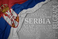 Waving colorful national flag of serbia on a gray background with important words about country. Concept royalty free stock photos