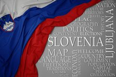 Waving colorful national flag of slovenia on a gray background with important words about country. Concept royalty free stock image