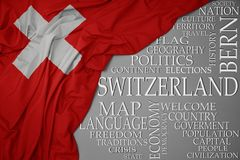 Waving colorful national flag of switzerland on a gray background with important words about country. Concept stock photos