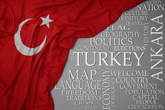 Waving colorful national flag of turkey on a gray background with important words about country. Concept royalty free stock photos
