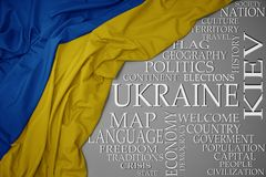 Waving colorful national flag of ukraine on a gray background with important words about country. Concept royalty free stock photo