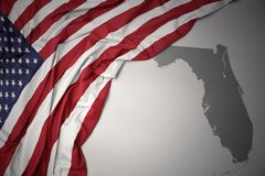 Waving national flag of united states of america on a gray florida state map background. Waving colorful national flag of united states of america on a gray stock photo