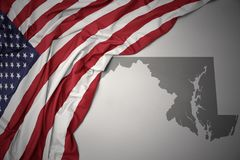 Waving national flag of united states of america on a gray maryland state map background. Waving colorful national flag of united states of america on a gray stock photography
