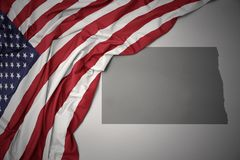 Waving national flag of united states of america on a gray north dakota state map background. Waving colorful national flag of united states of america on a royalty free stock images