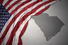 Waving national flag of united states of america on a gray south carolina state map background. stock photography