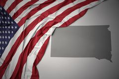 Waving national flag of united states of america on a gray south dakota state map background. royalty free stock photo