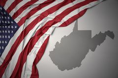 Waving national flag of united states of america on a gray west virginia state map background. Waving colorful national flag of united states of america on a royalty free stock photos