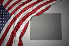 Waving national flag of united states of america on a gray wyoming state map background. Waving colorful national flag of united states of america on a gray stock photo
