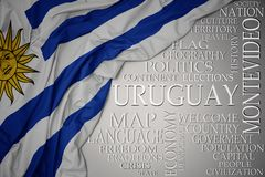 Waving colorful national flag of uruguay on a gray background with important words about country. Concept stock photography