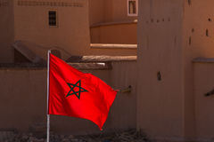 Waving Fabric Flag of Morocco with traditional building in backg Stock Photos