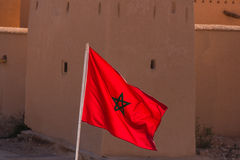 Waving Fabric Flag of Morocco with traditional building in backg Stock Image