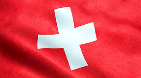Waving fabric texture of the flag of switzerland, red background and white cross. Symbol of swiss Royalty Free Stock Photography