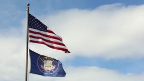 Waving federal and utah state flags stock video footage