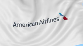 Waving flag of American Airlines against blue sky background, seamless loop. Editorial 4K animation stock video footage