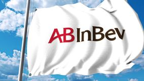 Waving flag with Anheuser-Busch InBev logo against clouds and sky. 4K editorial animation stock footage