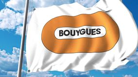 Waving flag with Bouygues logo against clouds and sky. 4K editorial animation stock video