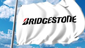 Waving flag with Bridgestone logo against clouds and sky. 4K editorial animation stock video