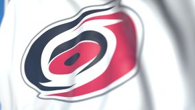 Waving flag with Carolina Hurricanes NHL hockey team logo, close-up. Editorial loopable 3D animation stock footage