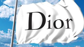 Waving flag with Christian Dior SE logo against clouds and sky. 4K editorial animation stock footage