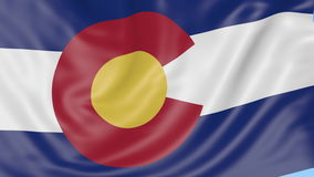 Waving flag of Colorado state against blue sky. Seamless loop 4K clip. ProRes stock video footage