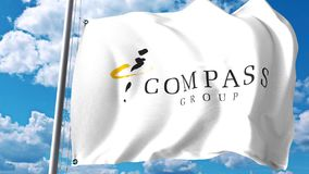 Waving flag with Compass Group plc logo against clouds and sky. Editorial 3D rendering Stock Images