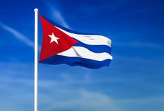 Waving flag of Cuba on the blue sky background. 3D rendered Stock Photos