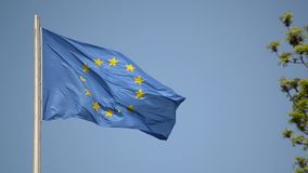 Waving flag of the European Union on the flagpole on blue sky background. EU flag flying on the wind. Symbol of EU waves proudly i stock video footage