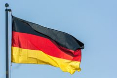 Waving flag of the Federal Republic of Germany in front of blue sky stock photography