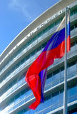 Waving flag in front of skyscraper Stock Images