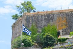 Waving flag of Greece in front of medieval fortress wall against Stock Photo