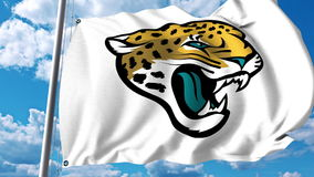 Waving flag with Jacksonville Jaguars professional team logo. Editorial 3D rendering Royalty Free Stock Photo