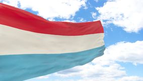 Waving flag of Luxembourg on blue cloudy sky. Royalty Free Stock Photo