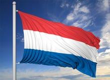 Waving flag of Netherlands on flagpole Royalty Free Stock Images