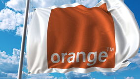 Waving flag with Orange logo against sky and clouds. Editorial 3D rendering. Waving flag with Orange logo against sky and clouds. Editorial 3D Royalty Free Stock Image