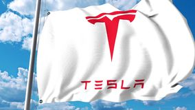 Waving flag of Tesla, Inc. against cloud and sky. Editorial clip