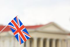Waving flag of United Kingdom and blurred building. On background Stock Photo