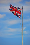 Waving flag of the United Kingdom. High up in blue sky with light cloud on a long white pole Royalty Free Stock Photo
