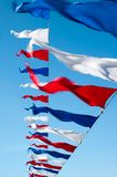 Waving flags. Small triangular waving flags against the sky Royalty Free Stock Photo