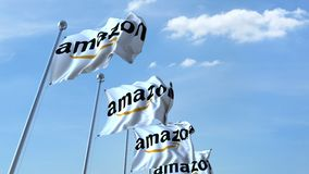 Waving flags with Amazon logo against sky, seamless loop. 4K editorial animation